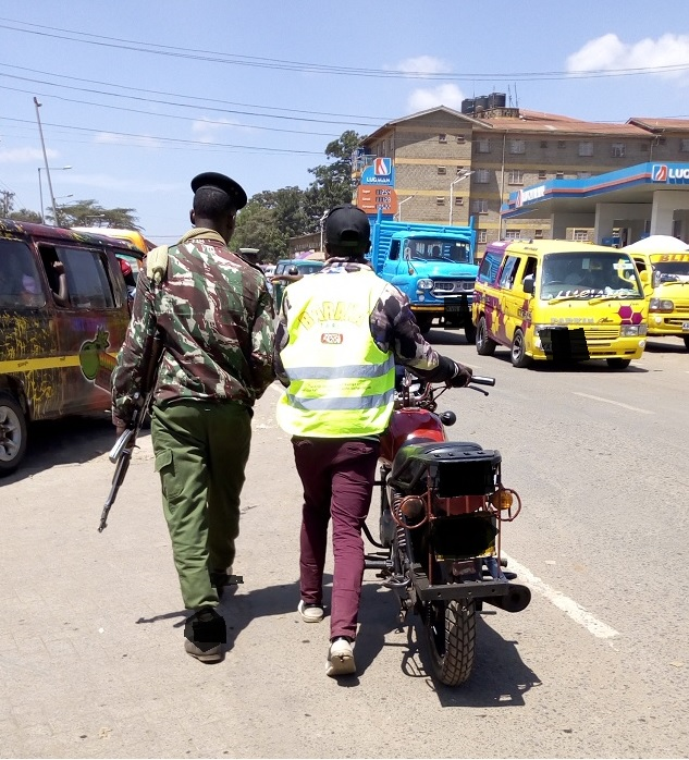 Boda boda rider and a police officer matching to the police station