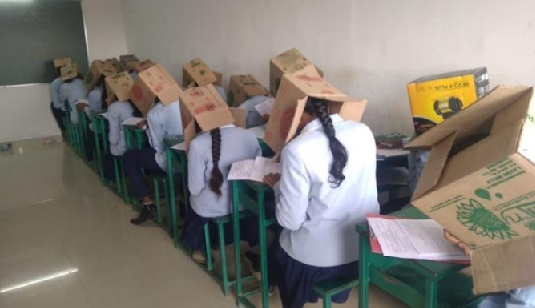 Indian students wear boxes on their heads to prevent cheating during exams