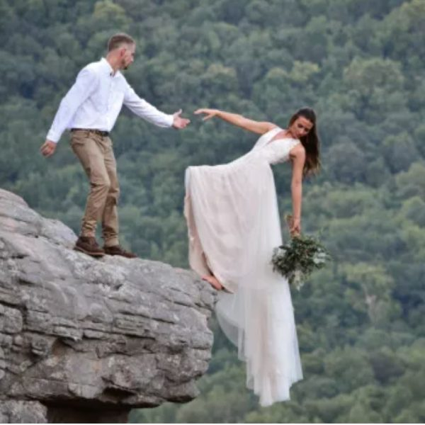 Bride and groom pose for wedding photo shoot hanging off the edge of a cliff (photos)